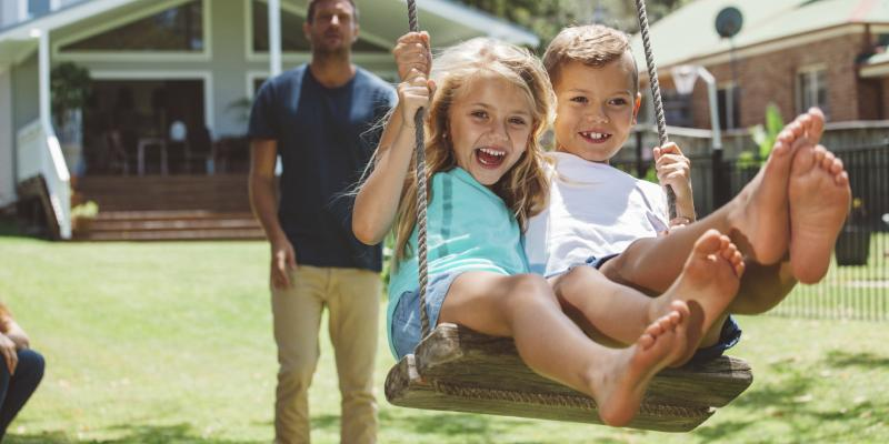 Two children on a swing being pushed by their father. They're enjoying a mosquito-free yard in Virginia Beach.